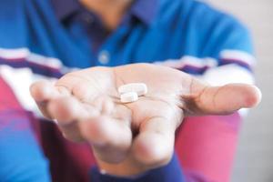 mão de homem segurando comprimidos