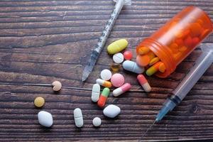 seringa, comprimidos e cápsulas na mesa foto