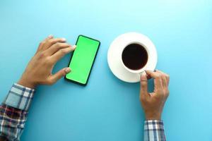 vista superior de um homem usando um telefone inteligente e bebendo café