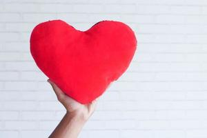 mão segurando o símbolo do coração vermelho sobre fundo branco