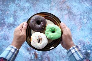 mão segurando um prato cheio de donuts vista de cima