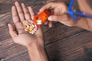 mão do homem com medicamento em fundo de madeira