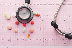 medicamentos prescritos e estetoscópio sobre fundo médico rosa