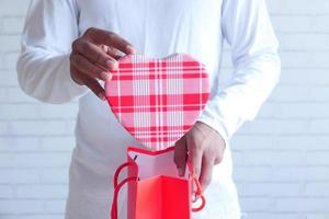 jovem colocando um presente em forma de coração em uma sacola de presentes foto