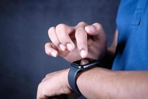 a mão do homem usando um relógio inteligente