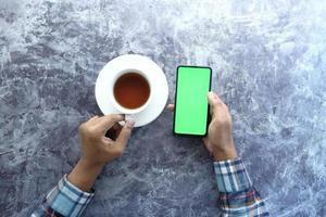 smartphone com tela verde e uma xícara de café