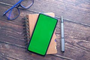 vista superior do smartphone e do bloco de notas na mesa