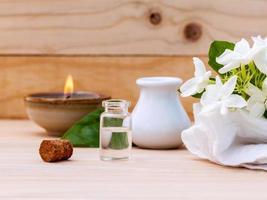 frasco de óleo de aromaterapia com flores de jasmim foto