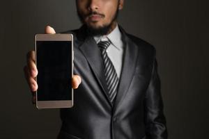 retrato de empresário mostrando smartphone contra fundo preto foto