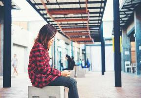 linda jovem hippie enviando mensagens de texto em seu smartphone, sentada em um banco
