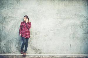 bela jovem hippie em pé falando no smartphone isolado com fundo grunge