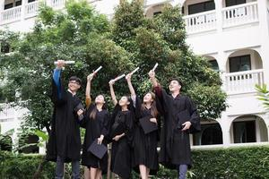 grupo de alunos bem-sucedidos jogando chapéus de formatura para o alto e comemorando foto