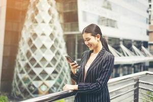 jovem empresária asiática usando smartphone móvel