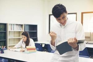 jovens estudantes asiáticos na biblioteca lendo um livro foto