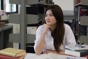 jovem estudante asiática sorrindo enquanto lê na biblioteca