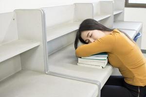 jovem estudante dormindo na biblioteca