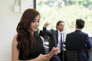 jovem empresária usando o telefone enquanto trabalha no escritório