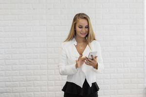 jovem empresária usando smartphone enquanto trabalha no escritório