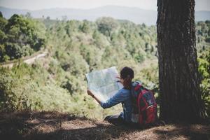 jovem alpinista lendo um mapa durante uma caminhada foto