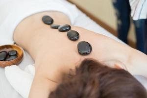 bela jovem recebendo massagem com pedras quentes em salão de spa