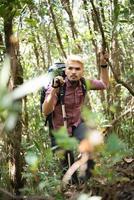 jovem caminhante ativo pela floresta em direção à montanha