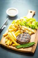 Bife grelhado com batata frita, molho e vegetais frescos foto