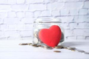 coração vermelho e moedas em uma jarra