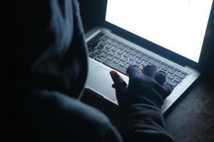 homem encapuzado roubando dados de laptop