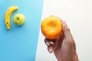 mão segurando frutas maduras de laranja em fundo azul