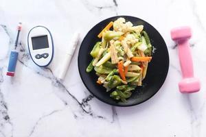 legumes cozidos no vapor e caneta de insulina e comida saudável na mesa