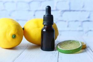 close up de uma garrafa de óleo e frutas cítricas foto