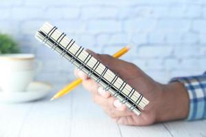 close-up de um homem segurando um bloco de notas