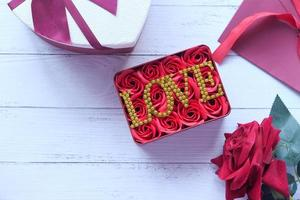 caixa de presente do dia dos namorados e flores na mesa de madeira foto