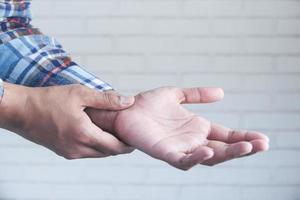 homem agarrando o pulso com dor