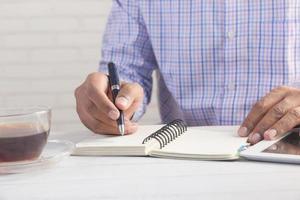 feche a mão do homem escrevendo no bloco de notas