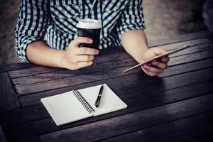 jovem usando tablet digital enquanto bebe café sentado na horta foto