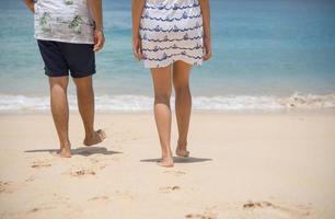 casal de namorados caminhando na praia foto