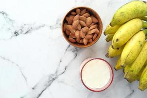 amêndoas e bananas em fundo de mármore foto