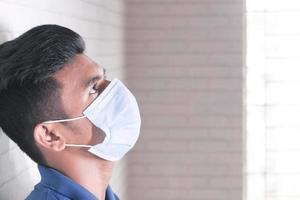 homem usando uma máscara encostado a uma parede foto