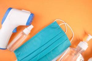máscaras cirúrgicas, termômetro e desinfetante para as mãos em fundo laranja