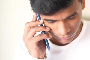 Feche a mão do jovem usando um telefone inteligente