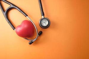 formato de coração e estetoscópio em fundo laranja