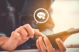 mão segurando um smartphone com ícones de comunicação foto