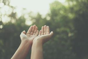 mãos colocadas juntas como uma oração em frente ao fundo verde da natureza foto