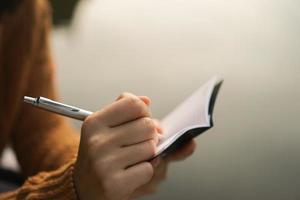 Mão de uma mulher escrevendo em um pequeno bloco de notas