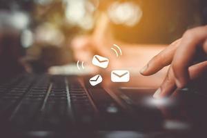 mão digitando em um teclado com ícones de comunicação