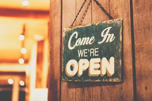uma placa de negócios que diz abrir na porta na entrada