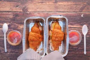 dois sanduíches de croissant em recipientes para viagem foto