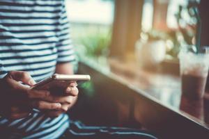mulher usando um smartphone em uma cafeteria com luz solar