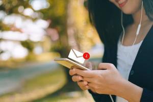 mão de uma mulher usando o smartphone para enviar e receber e-mail. foto
